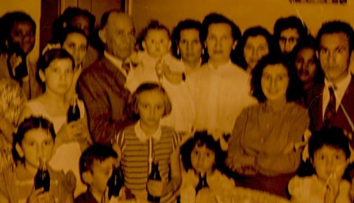 Em uma festa nos anos 50, Joaquim segura uma neta; Amélia está de camisa branca ao centro. Por que tão sérios?